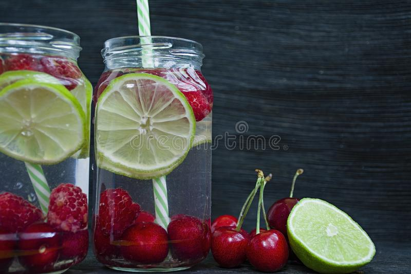 Bebida de restauración del verano con la fruta Bebida hecha de la cereza, frambuesa, cal Fondo de madera oscuro Espacio para el t fotografía de archivo