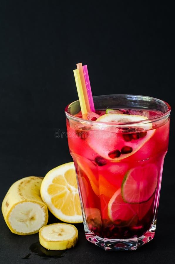 Bebida de restauración del verano con las pajas de beber, el granate y las rebanadas de frutas cítricas imagen de archivo libre de regalías
