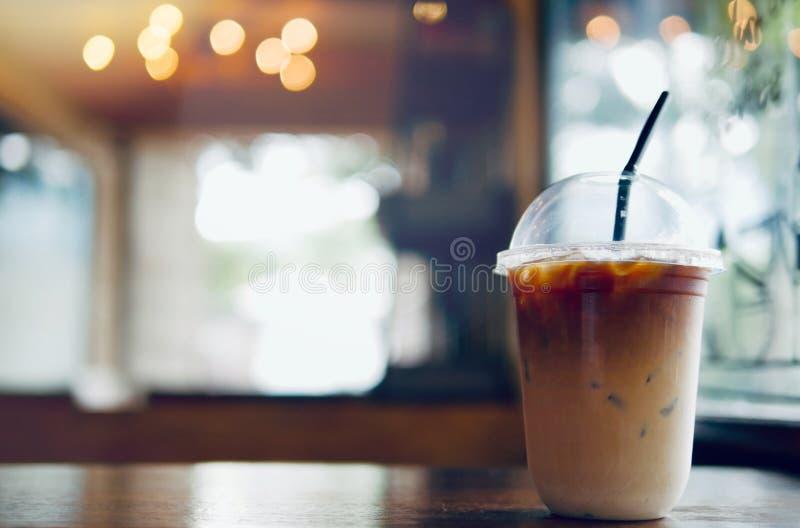 Bebida de restauración del verano del latte del café helado en llevarse la taza plástica en la tabla de madera con el fondo borro foto de archivo libre de regalías