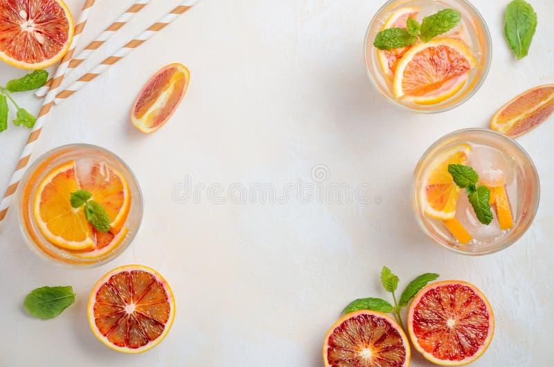 Bebida de restauración fría con las rebanadas de la naranja de sangre en un vidrio en un fondo concreto blanco foto de archivo libre de regalías