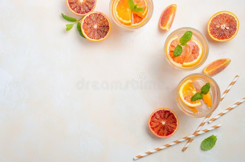 Bebida de restauración fría con las rebanadas de la naranja de sangre en un vidrio en un fondo concreto blanco fotos de archivo libres de regalías