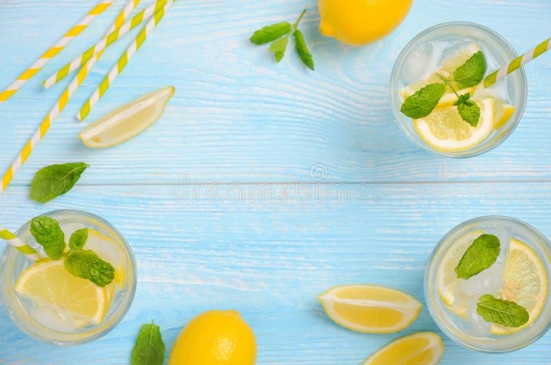 Bebida de restauración fría del verano con el limón y la menta en fondo de madera azul claro imagen de archivo