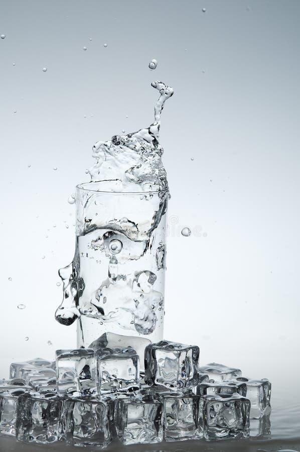Bebida del agua que salpica hacia fuera del vidrio imagen de archivo
