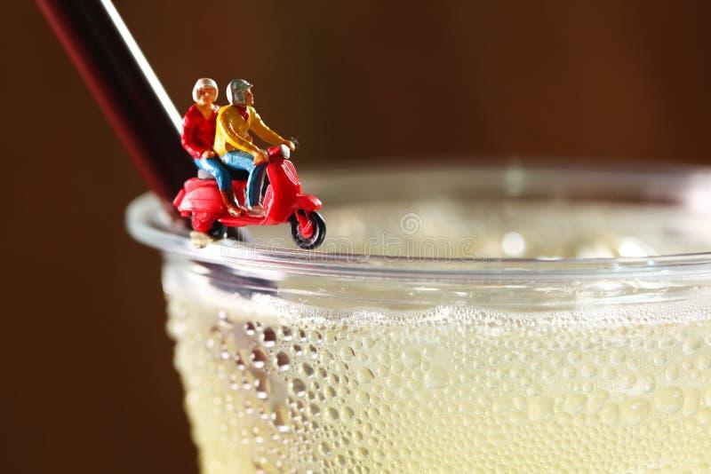 Bebida del alcohol en la taza plástica y la figura plástica miniatura escena foto de archivo
