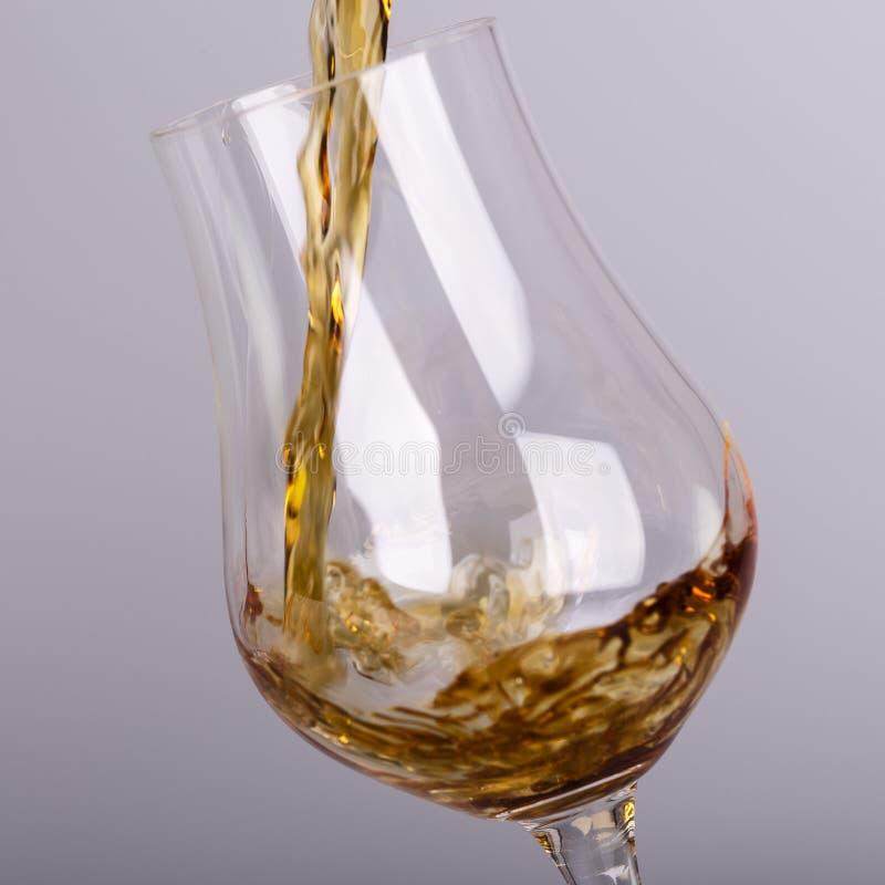 Bebida del alcohol que vierte en el vidrio aislado fotografía de archivo