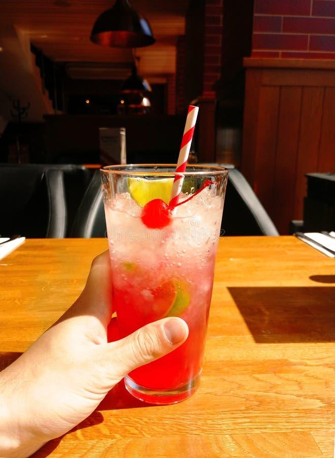 Bebida del coctail del alcohol con la paja de la cereza, de la cal y de la piruleta en la tabla en restaurante foto de archivo libre de regalías