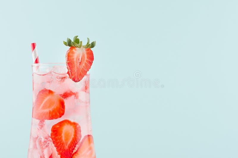 Bebida del detox de la fruta con las rebanadas rojas de la fruta, cubos de hielo, agua chispeante, paja rayada en vidrio misted e foto de archivo libre de regalías