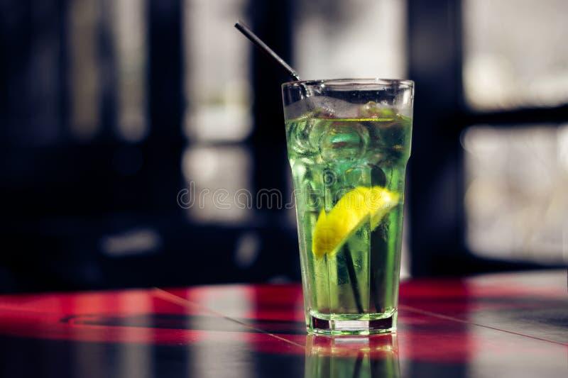 Bebida deliciosa del verano con una rebanada de limón en la tabla roja imagen de archivo libre de regalías