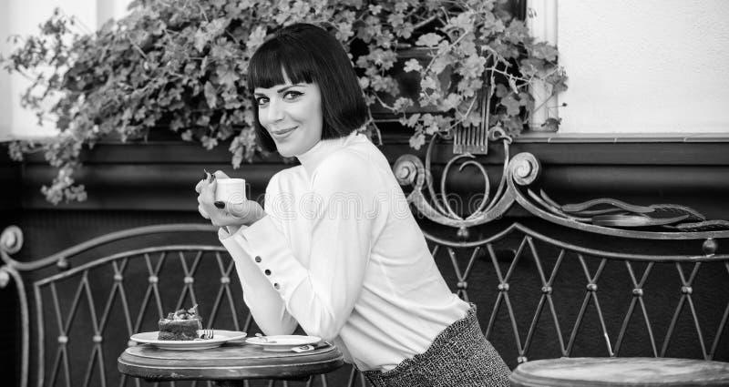 Bebida deliciosa y gastr?noma La muchacha relaja el caf? con caf? y el postre La morenita elegante atractiva de la mujer goza de  imagen de archivo