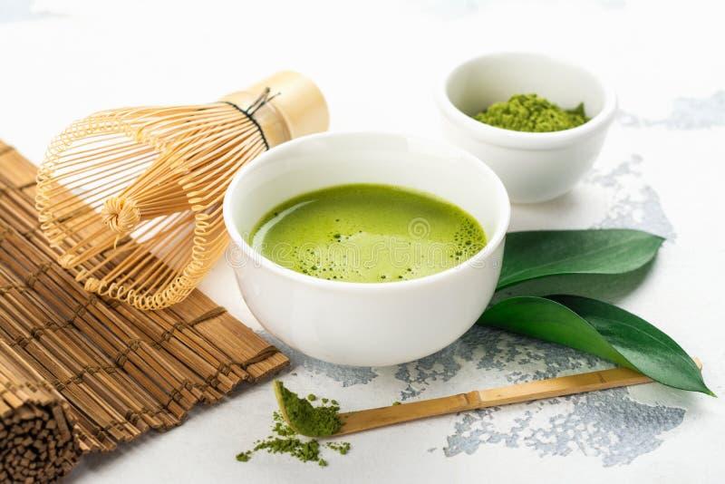 Bebida do chá do matcha e acessórios verdes do chá no fundo branco fotografia de stock royalty free