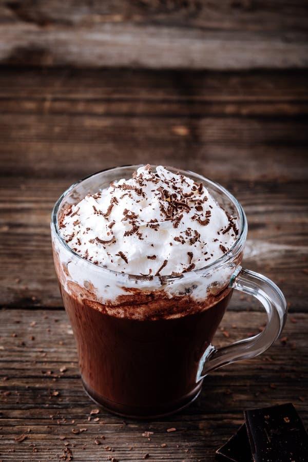 Bebida do chocolate quente com chantiliy em um vidro em um fundo de madeira fotos de stock royalty free