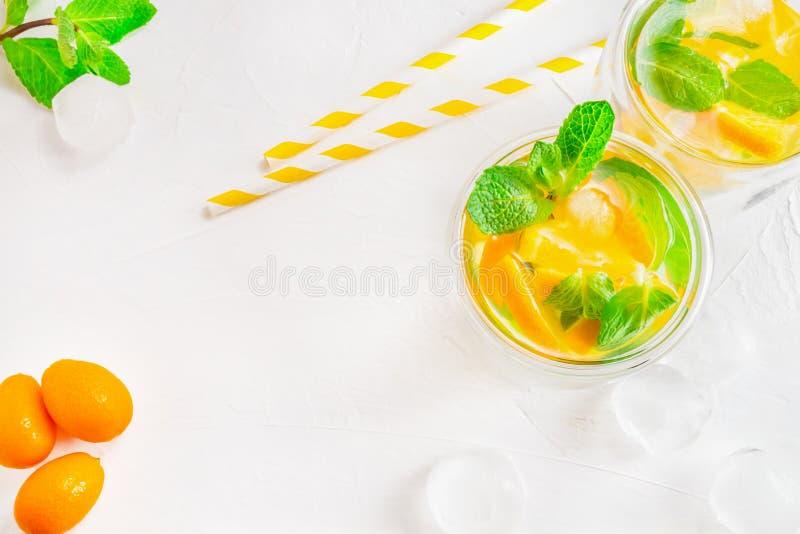 Bebida do citrino do verão com os cubos da laranja, do kumquat, da hortelã e de gelo no fundo branco Liso-configura??o, vista sup fotografia de stock