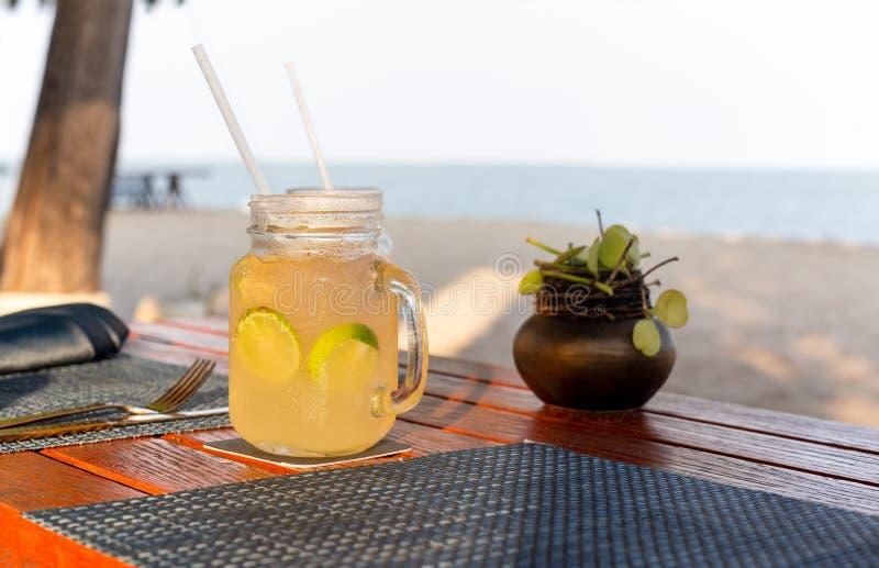 Bebida do limão e do mel com fatia de cal na bebida de refrescamento do verão da tabela fotografia de stock