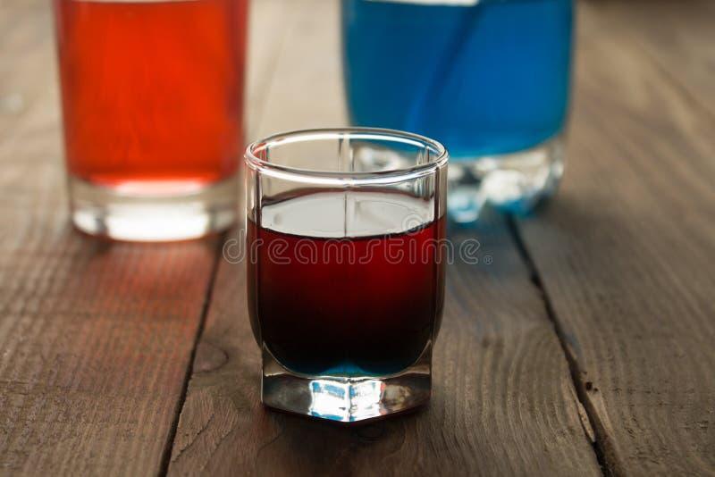 Bebida do tiro do álcool duas camadas vermelhas e azuis imagens de stock royalty free
