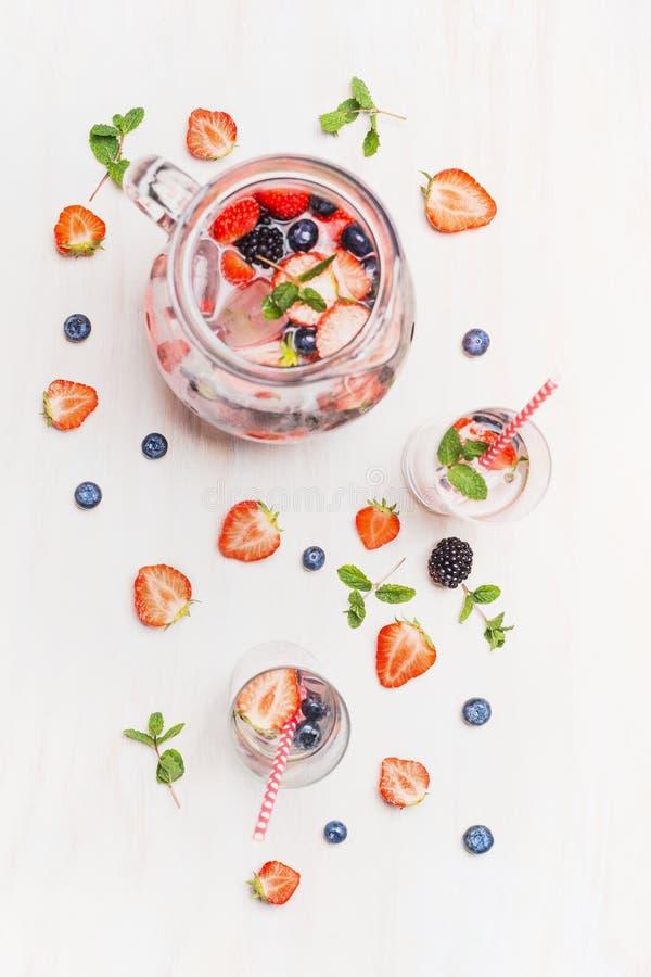 Bebida do verão com bagas e cubos de gelo Jarro ou jarro com bagas limonada, vidros, palha e ingredientes em b de madeira branco fotografia de stock