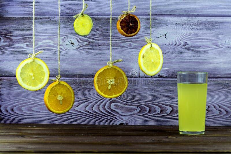 Bebida do verão Pendurando em fatias das cordas de limão, de laranja e de cal Um vidro da limonada imagens de stock