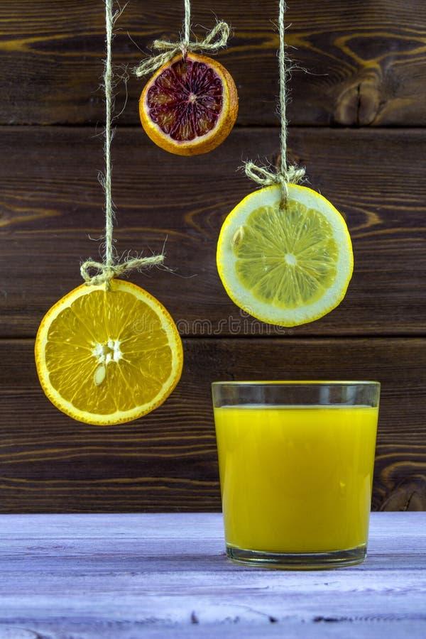 Bebida do verão Pendurando em fatias das linhas de limão, de laranja e de cal verão fresco, vidro do suco de laranja fotos de stock royalty free