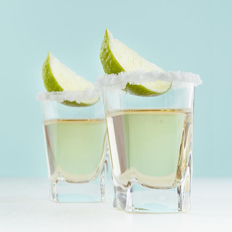 Bebida dourada mexicana tradicional do álcool do tequila com borda do cal e do sal no vidro disparado no fundo azul elegante da c fotografia de stock royalty free