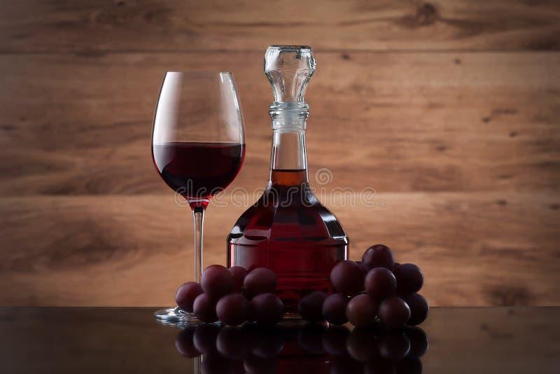 Bebida e alimento Copo de vinho, garrafa do vinho e uvas vermelhas imagem de stock royalty free