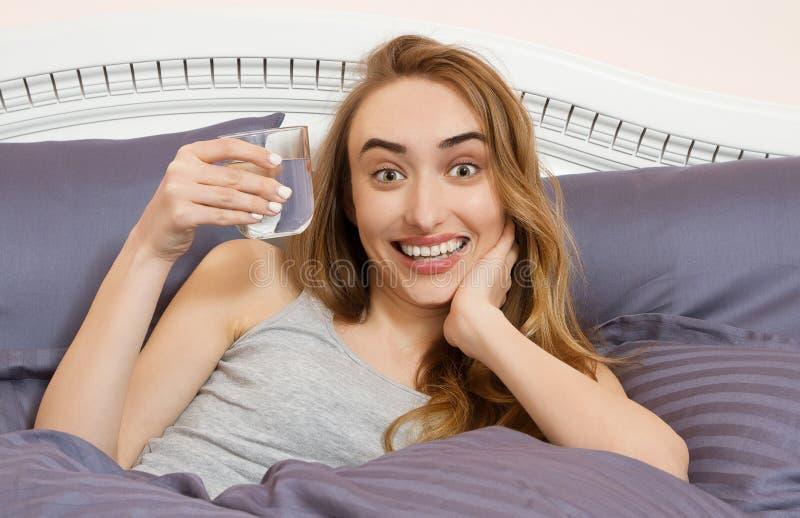 Bebida emocional feliz de la mujer al vaso de agua en el dormitorio de la mañana imágenes de archivo libres de regalías