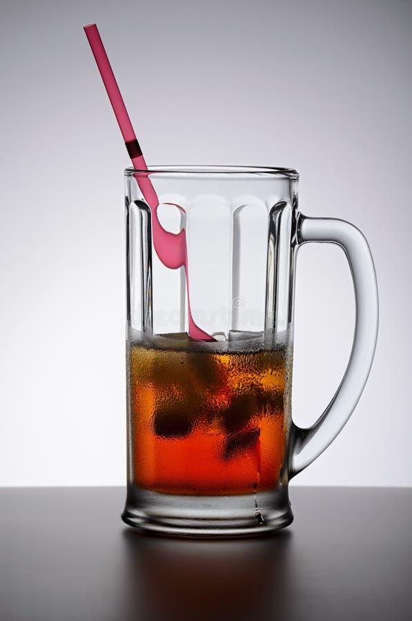 Bebida fría con hielo en la taza de cristal con la manija y el tubo de consumición en fondo ligero imagenes de archivo
