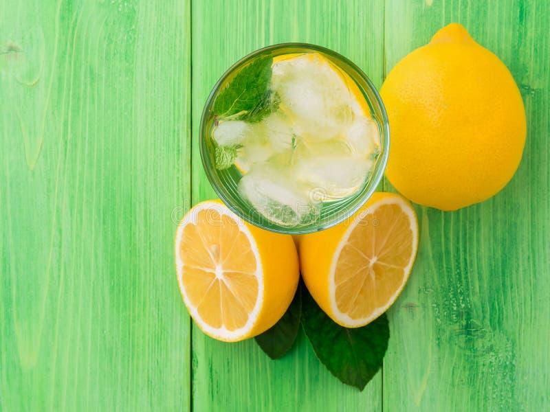 Bebida fría del agua, de los cubos de hielo, de la menta y del limón en un vidrio, limón fotografía de archivo