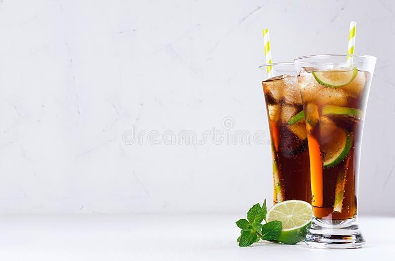Bebida fría fresca del verano de la cola, hielo, cal, menta de la hoja en el fondo blanco de la luz suave, espacio de la copia fotografía de archivo
