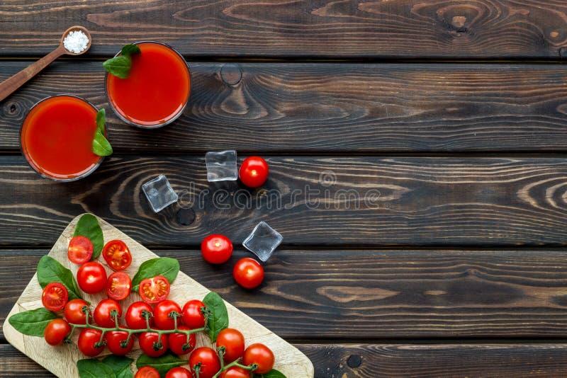 Bebida fresca con el tomate y el hielo en copyspace de madera de la opinión superior del fondo imagenes de archivo