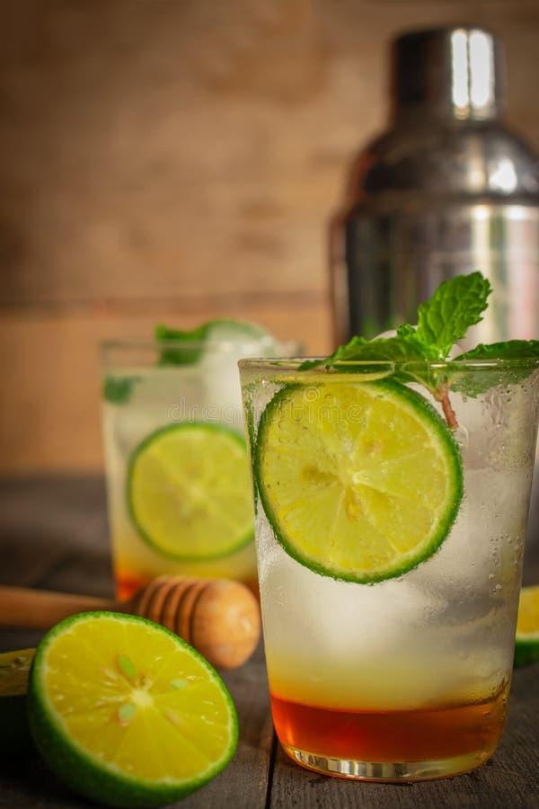 A bebida fresca da soda de Honey Lemon do gelo na tabela de madeira l? ? o mesmo objeto, fatia do lim?o, abanador de cocktail e d imagens de stock royalty free