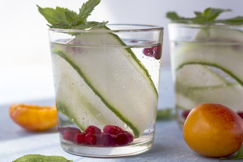 Bebida fresca fresca del detox con el pepino, bayas y melocotones o aprikotes imagen de archivo libre de regalías