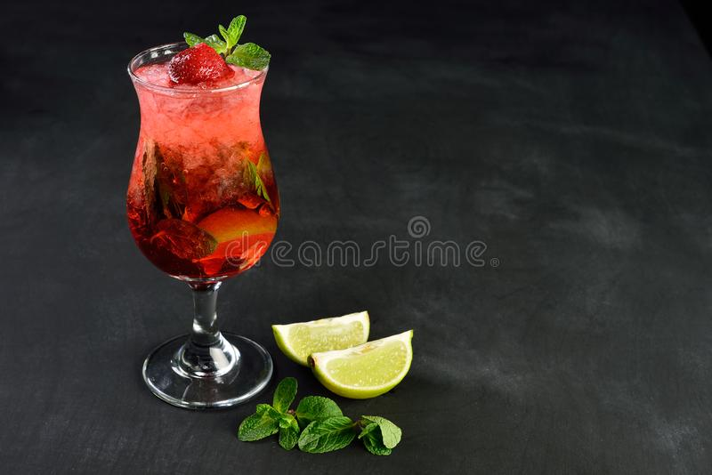 Bebida fresca do mojito da morango do verão com o gelo, servido na madeira preta fotos de stock royalty free