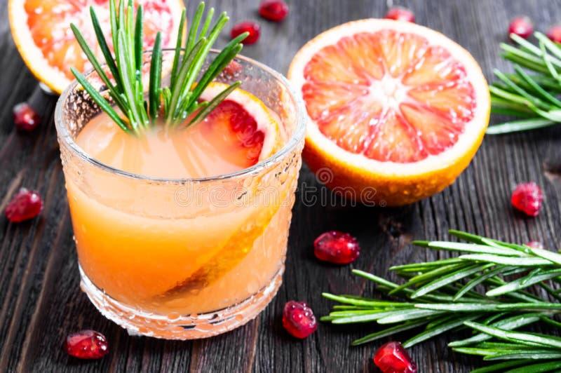 Bebida fresca do ver?o com laranja pigmentada e alecrins em um vidro no fundo de madeira escuro Foco seletivo foto de stock royalty free