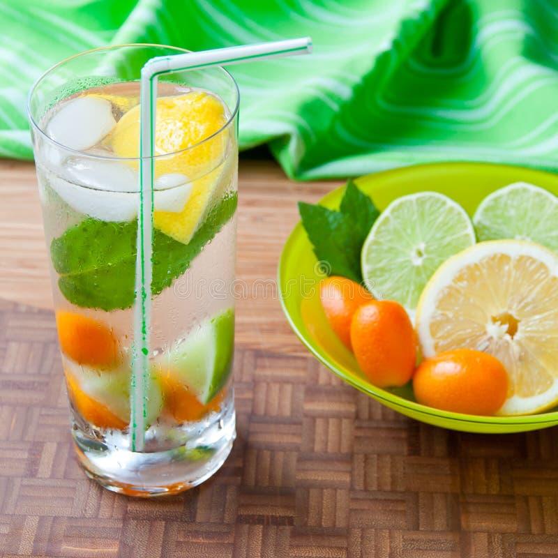 Bebida fresca fria com limão, cal, kumquat e hortelã. fotografia de stock