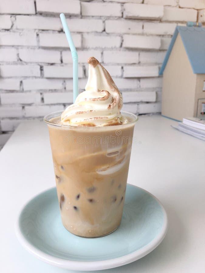 Bebida fresca na tabela de madeira, café do café do gelado com caramelo no copo plástico na placa pastel verde fotografia de stock royalty free