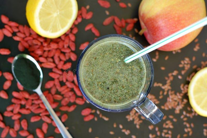 Bebida fresca sana del smoothie del goji chino rojo de la baya, del limón, del spirulina verde, de la linaza y de la manzana fotografía de archivo