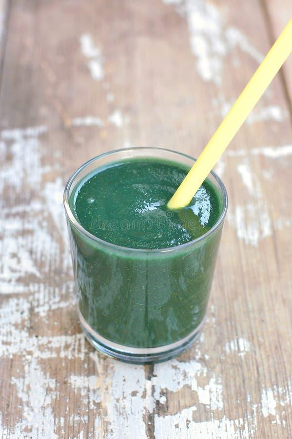 Bebida fresca saudável do batido do quivi, da pera e do cal no vidro com palha na tabela rústica de madeira fotografia de stock
