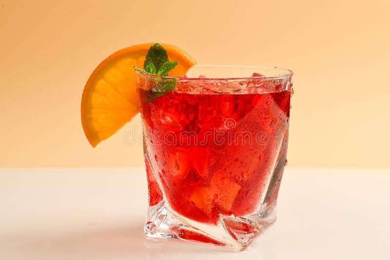 Bebida fresca vermelha com gelo, toranja e hortelã em um fundo bege imagens de stock royalty free