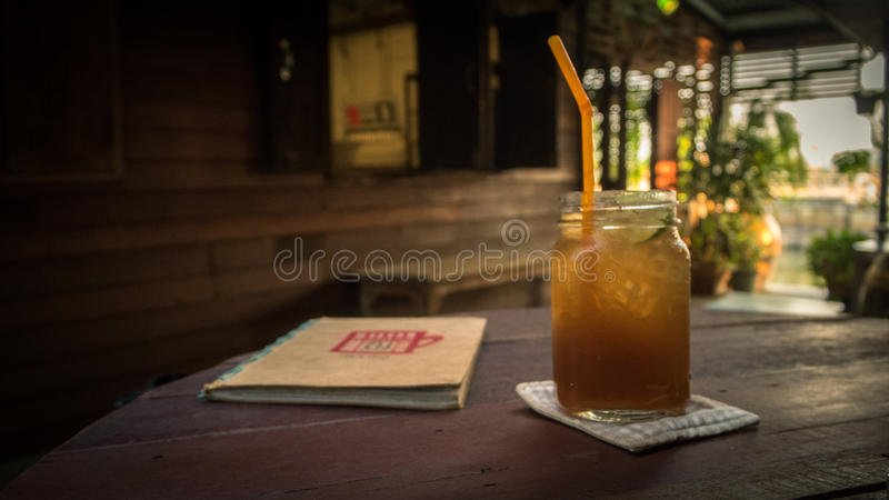 Bebida fria com um livro fotografia de stock