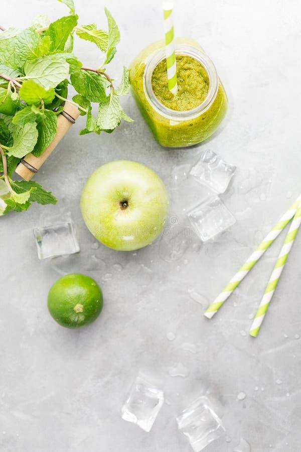 Bebida healty verde no frasco de pedreiro com maçã verde, hortelã, cal e os cubos de gelo de derretimento no fundo cinzento Conce imagens de stock royalty free