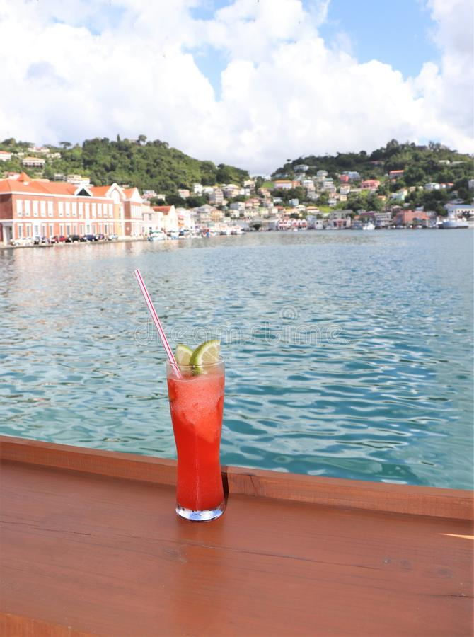 Bebida helada en un carril con el océano y escenas tropicales de la isla en el fondo imagenes de archivo