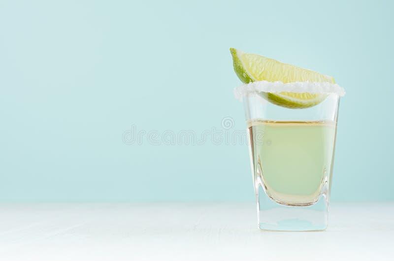 Bebida mexicana tradicional del alcohol - tequila en vaso de medida elegante con el borde de la sal y rebanada verde de la cal en foto de archivo libre de regalías