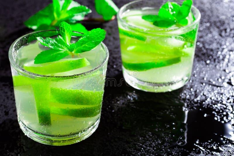 Bebida Mojito do verão, com cal e hortelã, em um fundo preto com gotas da água imagens de stock