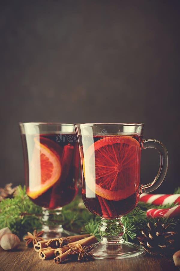 A bebida morna do Natal tradicional ferventou com especiarias o vinho nos vidros no fundo de madeira com ramos do pinho foto de stock