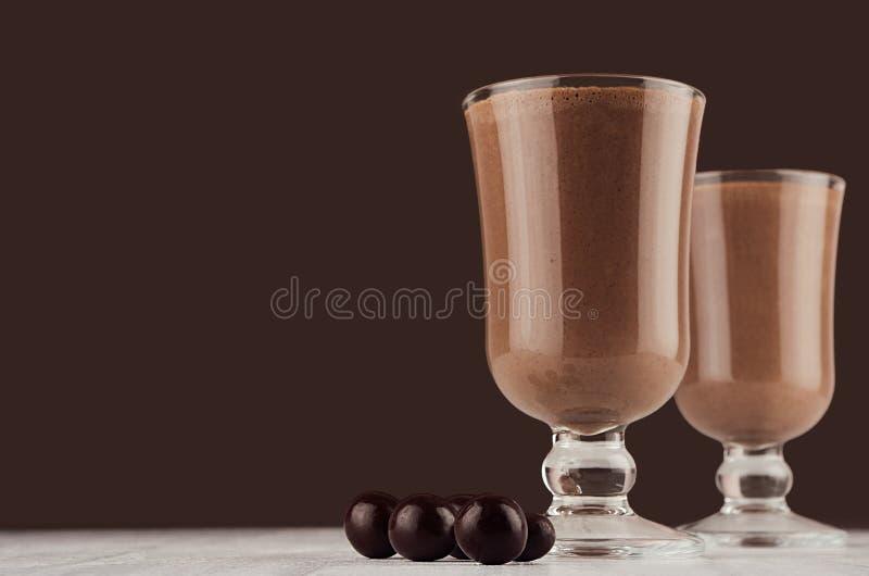 Bebida morna do outono - cacau quente com os doces de chocolate redondos no fundo marrom escuro, espaço da cópia imagem de stock