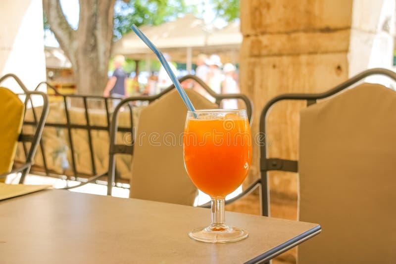 Bebida na tabela da praia, água fresca fresca do suco de laranja do verão para o abrandamento batidos frutados e agitações na tab imagem de stock