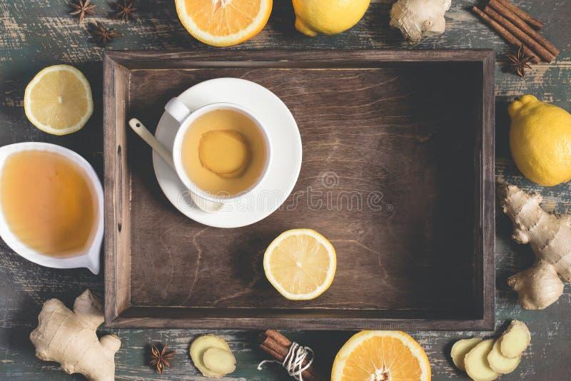 Bebida natural de impulso da vitamina da imunidade quente do gengibre com limão, mel e canela na bandeja e nos ingredientes fotografia de stock royalty free