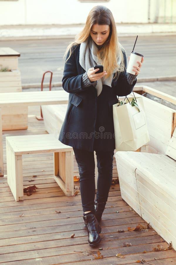 A bebida nova da mulher elegante leva embora o café e lê a mensagem no telefone celular foto de stock
