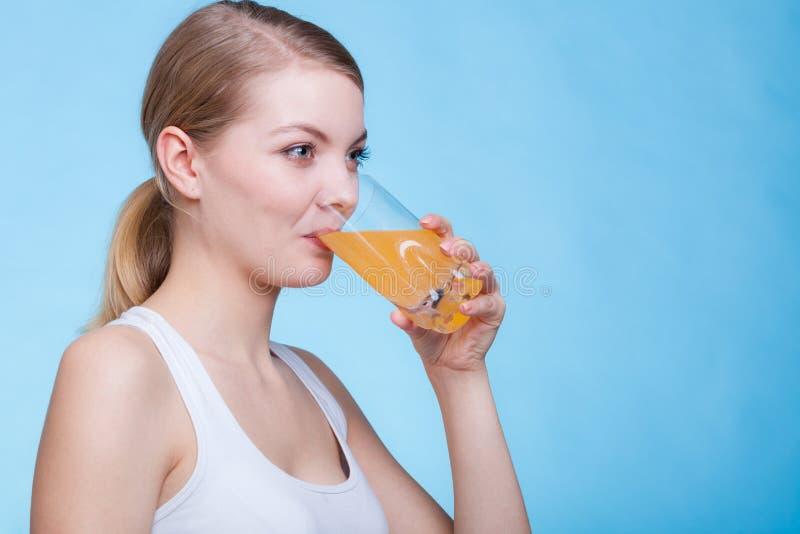 Bebida o jugo con sabor a naranja de consumición de la mujer imagen de archivo