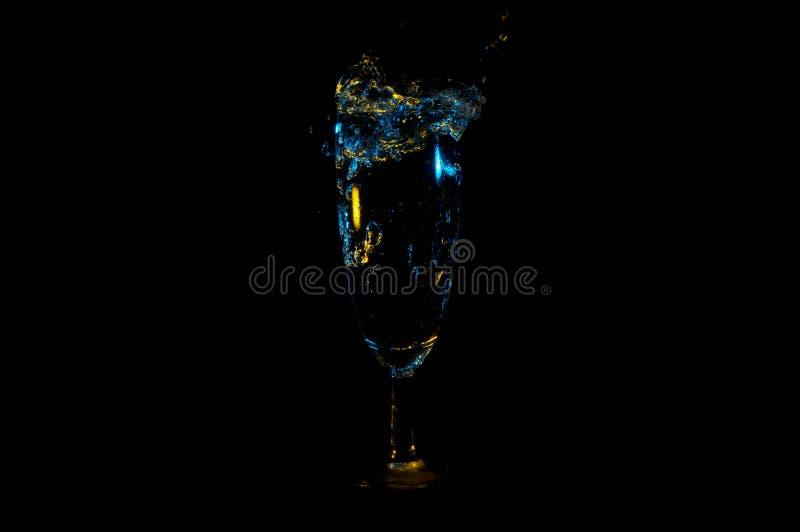 Bebida que salpica fuera de un vidrio provenido alto bajo luces amarillas y azules aisladas en un fondo negro fotos de archivo