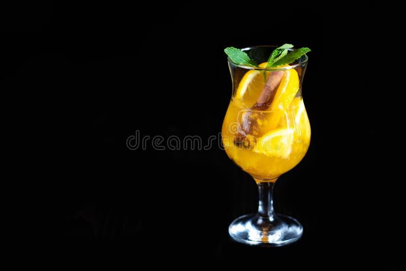 Bebida que se calienta del invierno con los pedazos de naranja y de especias en un fondo negro Porción del restaurante imagen de archivo libre de regalías